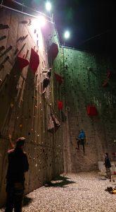 Mænd klatre på oplyst klatrevæg på Friluftscenter Sprækkebjerg.