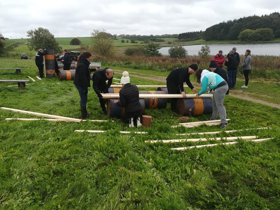 Kursister hjælper hinanden med at bygge tømmerflåde.