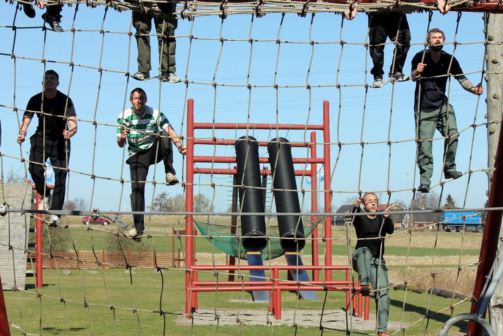 Mænd kravler i højt net.