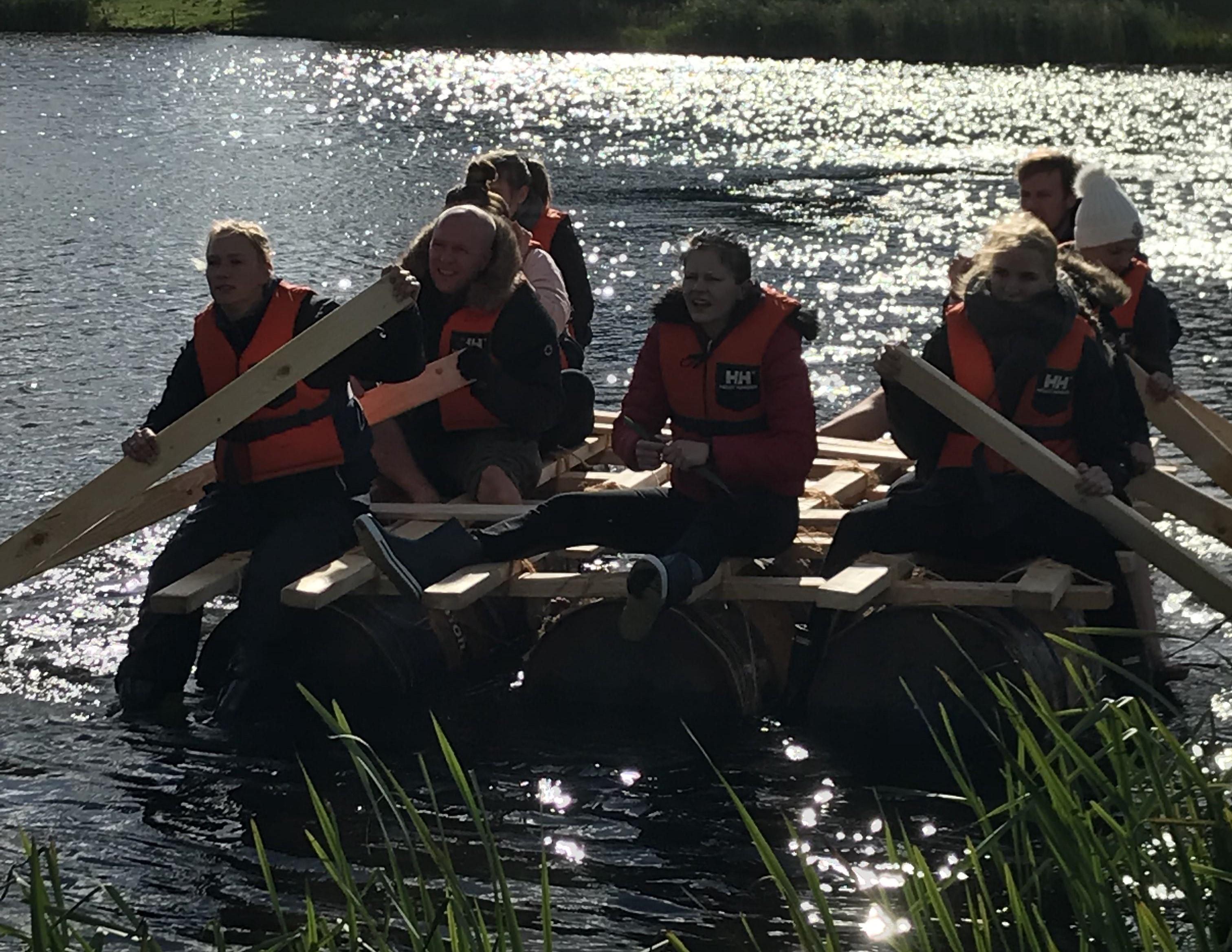 Kursister i vandet med selvkonstrueret tømmerflåde.