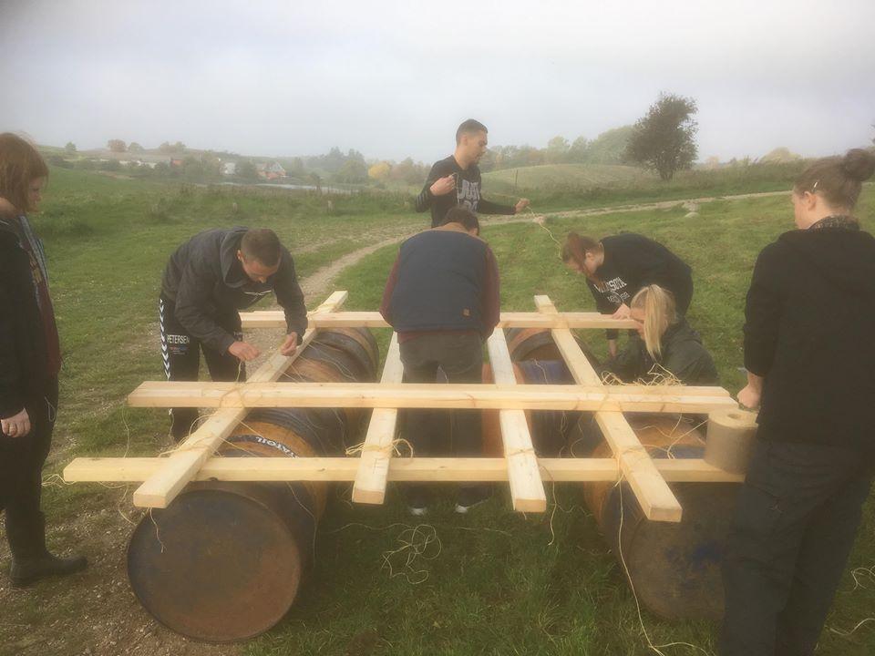 Syv kursister hjælper hinanden med at bygge tømmerflåde.